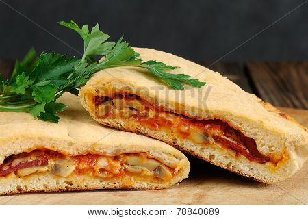 Pizza Calzone With Mushrooms And Fresh Parsley