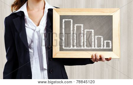 Young woman holding frame with decreasing graph
