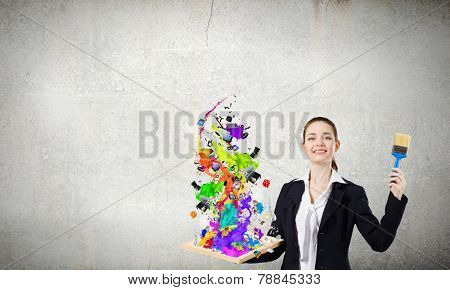 Young businesswoman holding paint brush and wooden frame