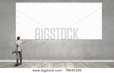 Rear view of businessman fixing blank white banner on wall