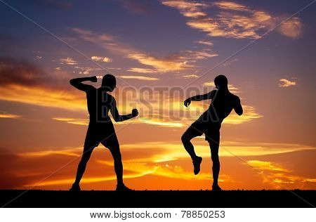 Silhouettes Of Two Fighters On Sunset Fiery Background