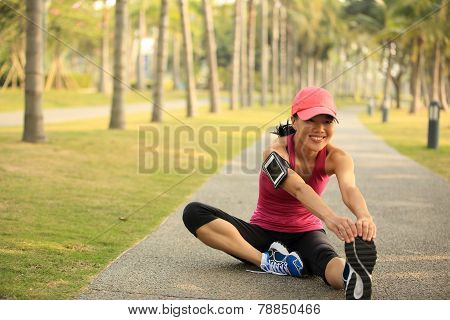 woman runner stretching legs outdoor