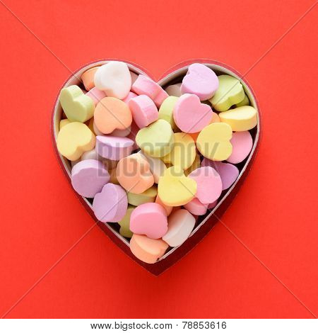 High angle view of a bunch of pastel candy hearts in a heart shaped box for Valentines Day. Square format on a red background, the candies are blank.