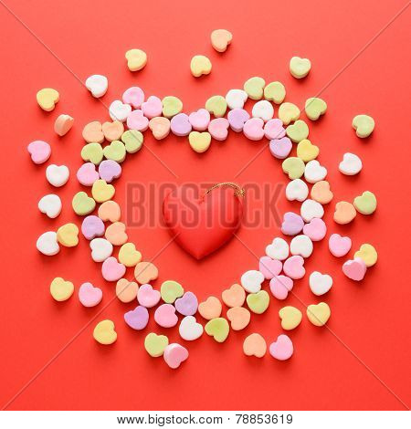 High angle view of a bunch of candy hearts in the shape of a heart surrounding another fabric heart. Square format on a red background. Valentines Day and Love concept.