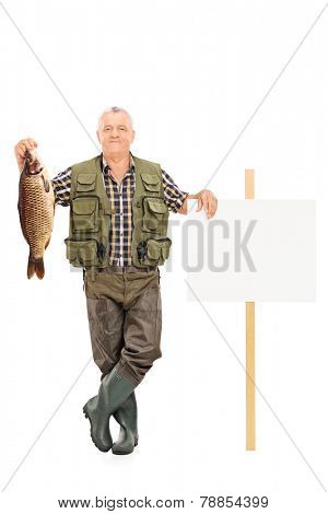 Full length portrait of a smiling mature fisherman holding a big fish next to a panel isolated on white background