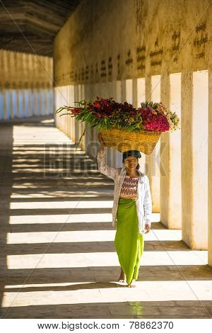 Unidentified Myanmar woman put the flower basket on her head at Shwezigon temple