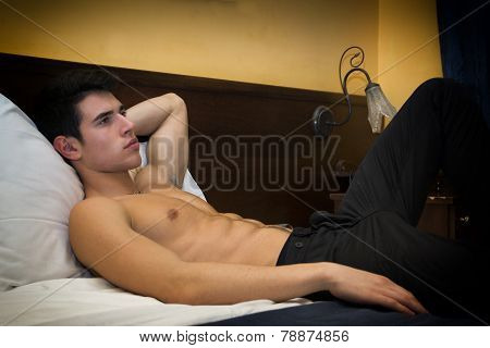 Handsome Shirtless Athletic Young Man In Bed At Night