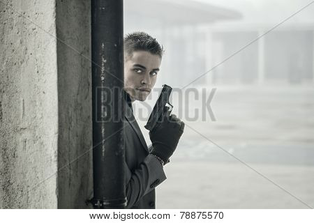 Young Detective Or Policeman Or Mobster In An Urban Setting Holding A Gun