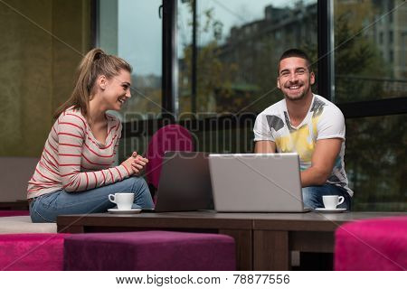 Happy Teenagers Using Laptop In Cafe