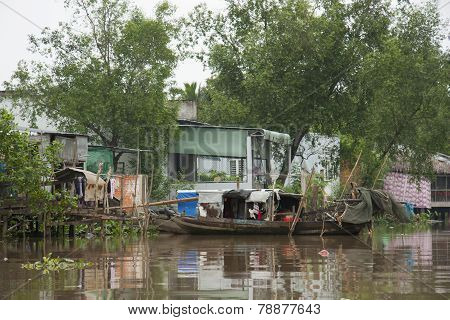 Houses on wooden stilts and old boat in Mekong Delta