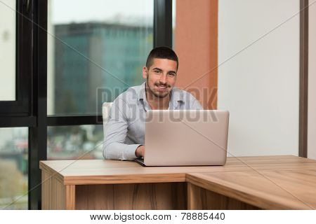 Happy Male Student In Library With Laptop