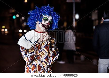 Crazy ugly grunge evil clown in town on Halloween making people shock and scared