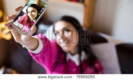 Happy pretty girl woman taking a selfie using smartphone,taking self portrait with her smart phone