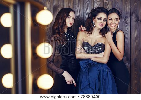 Three Beautiful Smiling Girls In Luxurious Dresses And Bijou
