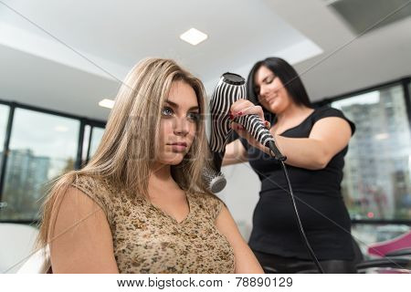 Hair Stylist Using Dryer On Woman In Salon