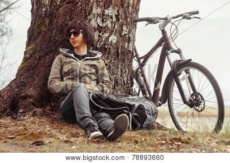 Hiker woman resting near the tree