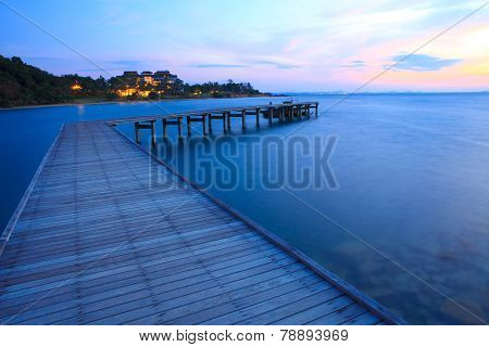 beautiful sea scape and wooden port against sun risting sky