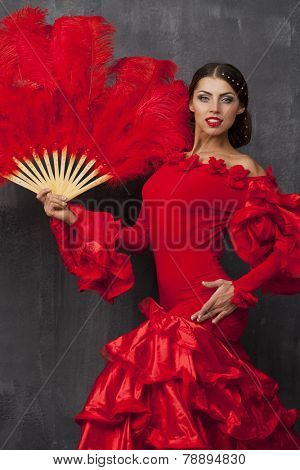 Sexy Woman traditional Spanish Flamenco dancer dancing in a red dress with fan
