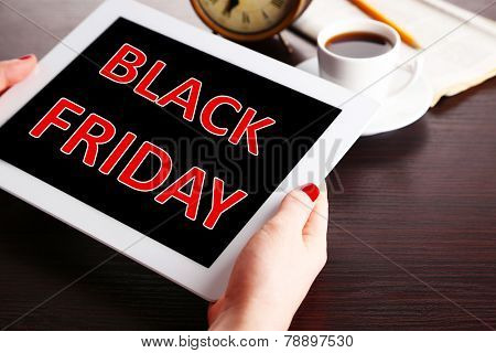 Hands holding tablet with Black Friday text on screen, Black Friday concept