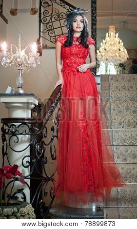 The beautiful girl in a long red dress posing in a vintage scene. Young beautiful woman in red