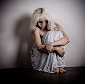 stock photo of domestic violence  - Scared woman sitting by the empty wall - JPG