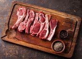 stock photo of pepper  - Raw fresh lamb ribs with pepper and cumin on wooden cutting board on dark background - JPG
