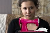 picture of gril  - Toy sewing machine with a gril in a blurred background - JPG