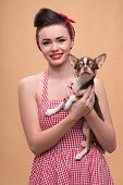 stock photo of headband  - Portrait of pretty brunette  girl in rose dress and red headband   in retro style  with Chihuahua smiling looking at camera waist up - JPG