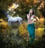 picture of beautiful horses  - Young women in a blue long skirt and white bra at sunset in forest with a white horse in background  - JPG