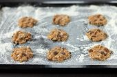 picture of baked raisin cookies  - uncooked oatmeal cookies with raisins on baking tray - JPG