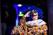 stock photo of halloween  - Crazy ugly grunge evil clown in town on Halloween making people shock and scared - JPG
