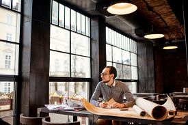 stock photo of cafe  - Creative architect thinking on the big drawings in the dark loft office or cafe - JPG