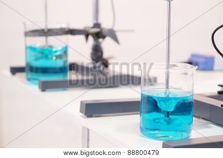 Laboratory equipment. Blue chemical substance in the beaker. Laboratory stirrers