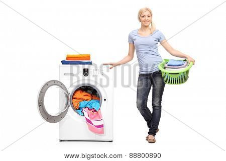 Full length portrait of a young woman holding a laundry basket full of folded clothes and posing next to a washing machine isolated on white background