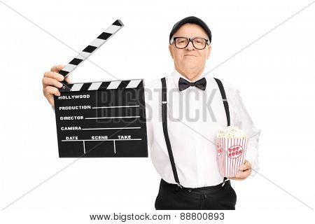 Mature movie director holding a clapperboard and a box of popcorn isolated on white background