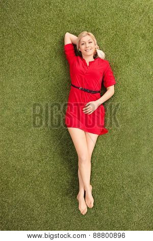 Vertical shot of an attractive blond woman in a red dress lying on grass in a field and looking at the camera