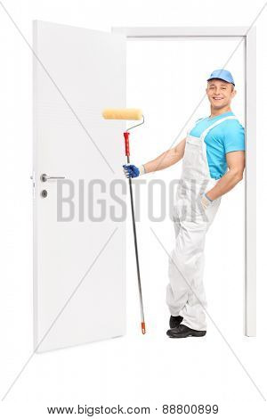 Full length portrait of a young painter holding a paint roller and leaning on the frame of an opened door isolated on white background