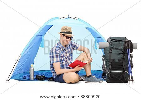 Young male camper reading a book seated on the ground with a blue tent behind him and a large backpack beside him isolated on white background