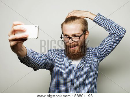 Life style concept: a young man with a beard  in shirt holding mobile phone and making photo of himself while standing against grey background.