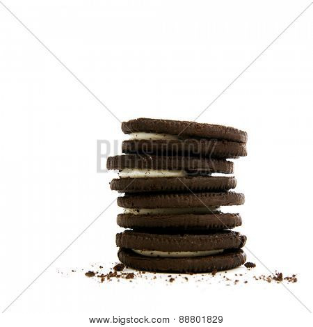 Chocolate cookies with creme filling and crumbs on white background