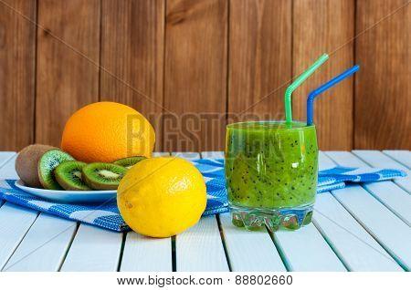 Healthy homemade kiwi juice in glass and fresh orange, lemon, kiwifruit on light wooden background.