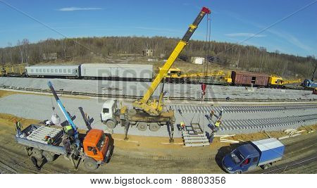 Building machines and crane with sleepers at construction of new railway next to wagons, aerial view
