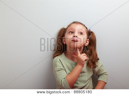 Fun Grimacing Girl Thinking And Looking Up On Blue Background