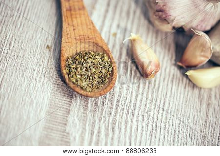 Garlics and oregano on table wooden background