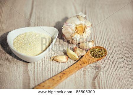 Garlics,parmesan, oregano on table wooden background