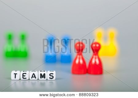 Cube Letters Show Teams  In Front Of Unsharp Figures