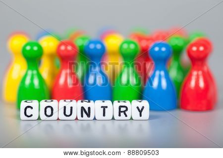Cube Letters Show Country  In Front Of Unsharp Figures