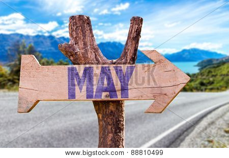 May wooden sign with road background