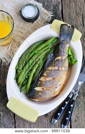 Baked fish with green beans on a wooden table