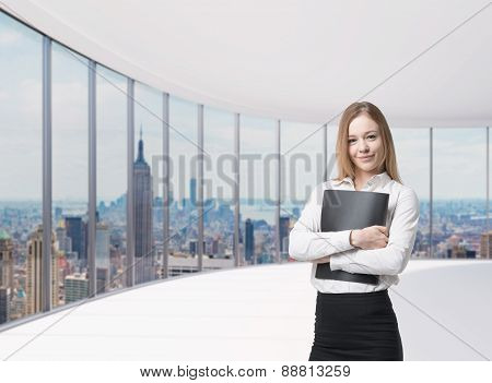 Young Beautiful Business Lady Is Holding A Black Document Case. New York Panoramic Office. A Concept